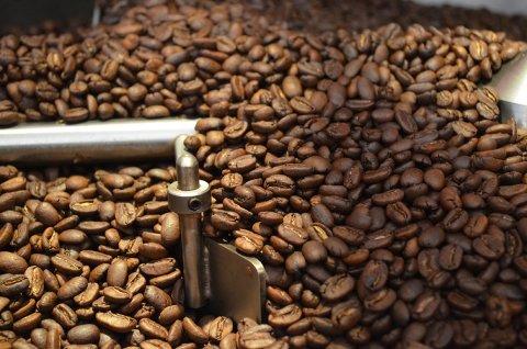 Zu sehen sind zahlreiche braune Kaffeebohnen. Zwischen den Bohnen ist ein metallenes Rohr zu erkennen.