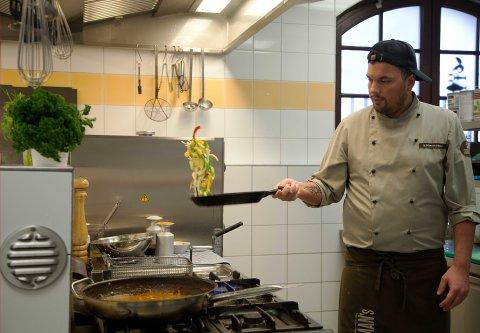 Ein Koch schwenkt Zutaten in einer Pfanne