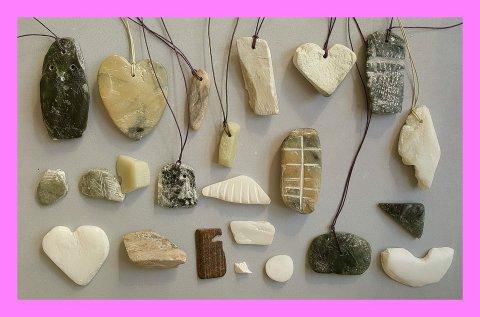 Geschnitzte Specksteine an Bändern, die unterschiedliche Formen haben.
