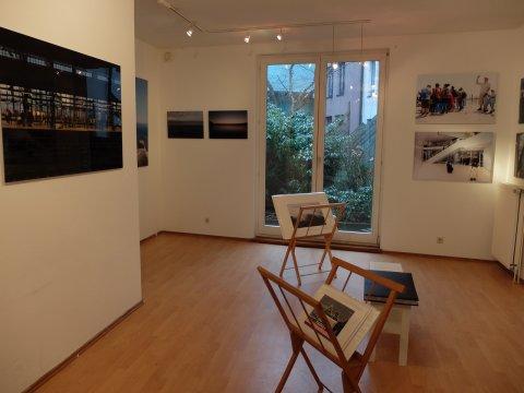 Galerie mit großen Fotografien an den Wänden und in zwei Holzständern in der Mitte des Raumes.