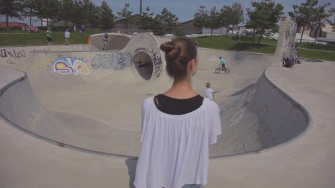 Eine Frau in weißem Oberteil mit Dutt ist von hinten zu sehen. Sie sitzt inmitten eines Skateparks, in dem Kinder auf Rädern und Rollern fahren.