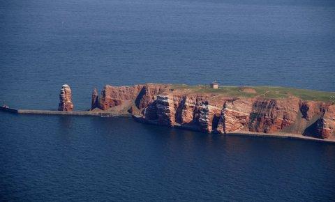 """Eine Luftaufnahme der roten Gesteinsklippen mit der """"Langen Anna"""" links im Bild."""