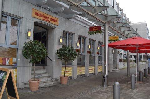 """Das spanische Restaurant """"Mucho Más"""" von außen. Große rote Sonnenschirme stehen vor der Tür """"Am Wall 136""""."""