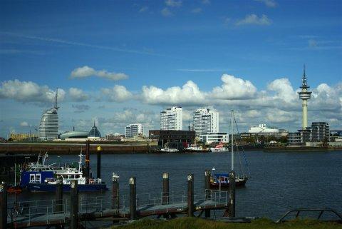 Bremerhavens Skyline ist in Form von Gebäuden und einem Turm im Hintergrund zu sehen. Davor ist ein Wasserkanal zu sehen. Im Vordergrund führt ein Steg zum Wasser. Einige Schiffe sind links im Bild festgemacht.