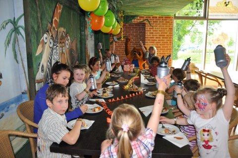 Kinder sitzen an einem Tisch in der Spielcoolisse und essen Kuchen. Sie heben alle eine Trinkflasche hoch.