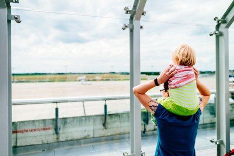 Eine Frau trägt ein Kind auf ihren Schultern. Beide gucken durch eine Scheibe nach draußen auf das Flughafengelände.