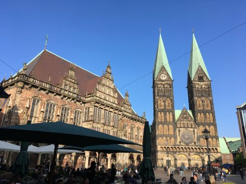 Das Bremer Rathaus und der Bremer Dom und der Marktplatz, auf dem Leute in einem Café sitzen