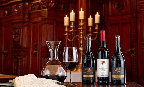 In einer Reihe: Karaffe und Glas mit Rotwein sowie drei Weinflaschen