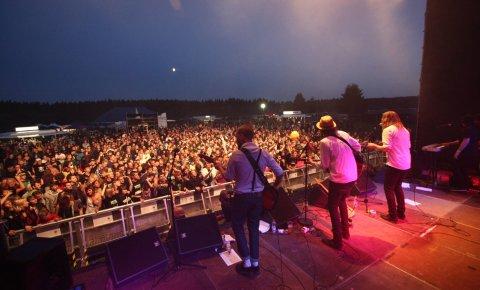 Eine Band steht auf der Bühne und es wurde in die Menschenmenge fotografiert.