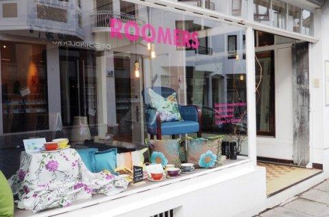 Das Schaufenster von draußen mit bunten Kissen und Tassen bestückt