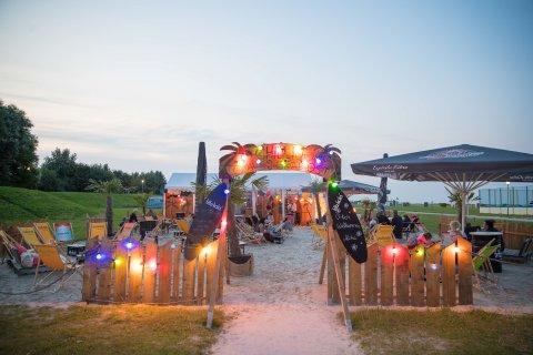 Ein Eingangstor mit einem Zaun aus Holz, das mit einer bunten Lichtergirlande versehen ist, steht im Vordergrund. Dahinter ist ein abgegrenzter Bereich mit Sand, Liegestühlen, einem kleinen Holzhaus und Personen zu sehen.