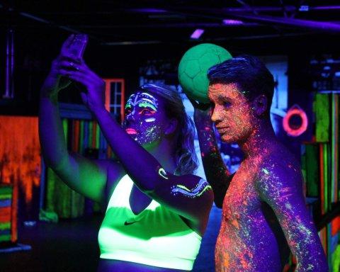 Auf dem Foto sind zwei Jugendliche abgebildet, die im Dunkeln ein Selfie machen. Beide sind mit Neonfarben verschmiert und schauen in die Kamera.
