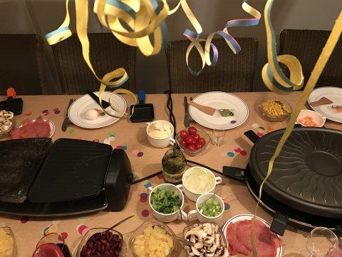 Ein feierlich gedeckter Tisch mit zwei Raclette-Geräten.