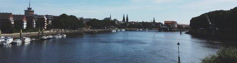 Der Ausblick auf einen Fluss, Häuser und einer weiteren Brücke im Hintergrund. Schiffe liegen an der Seite