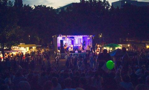 Eine Bühne mit Band und Publikum im Sommer, draußen im Dunklen.