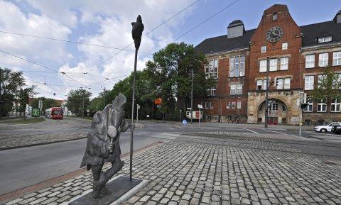 Die Bronzestatue in der Mitte des Leibnizplatzes in Bremen, ein Mensch mit Vogelgesicht schaut in einen Spiegel.