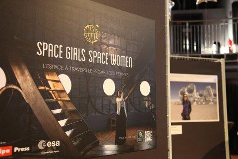 Ein Plakat, das eine Frau zeigt, die durch ein Teleskop schaut.