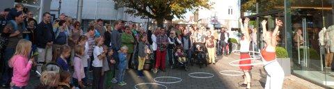 Eine größere Menschen Gruppe steht im Halbkreis um zwei Straßenkünstlerinnen in Vegesack, die eine Hula-Hoop-Nummer zeigen.