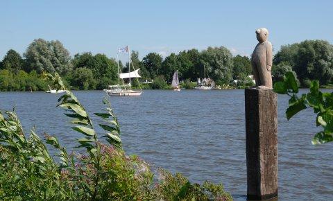 Ausblick auf den Vörder See mit der Skulptur Seemann im Vordergrund, im Hintergrund die Seebühne.