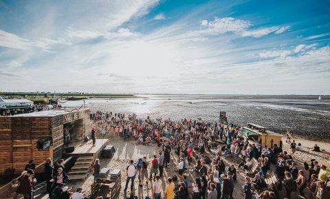 Das Watt En Schlick Festival am Wattenmeer bei Ebbe mit einer Menschenmenge vor einer kleinen Bühne.