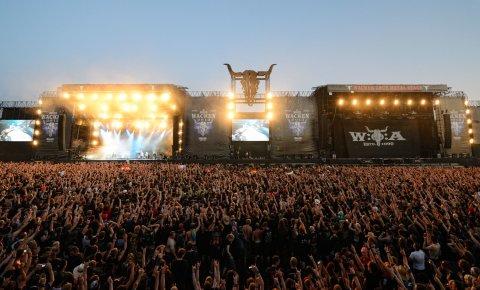 Eine große Menschen Menge steht vor den Bühnen auf einem Musikfestival.