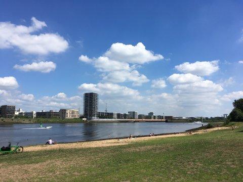 Blick auf einen Badestrand mit Wiese am Ufer der Weser und der Überseestadt auf der gegenüberliegenden Uferseite