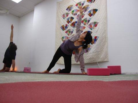 Zwei Personen machen Yoga auf Matten in einem weißen Raum und an der Wand hängt ein bunter Wandteppich