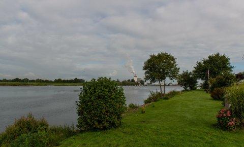 Ein Blick vom Ufer auf die Weser, im Hintergrund raucht der Schornstein eines Unternehmens.