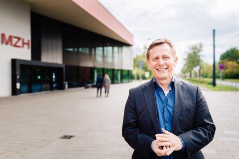 Auf dem Bild ist ein lächelnder Mann zu sehen. Im Hintergrund befindet sich ein Gebäude der Universität Bremen.