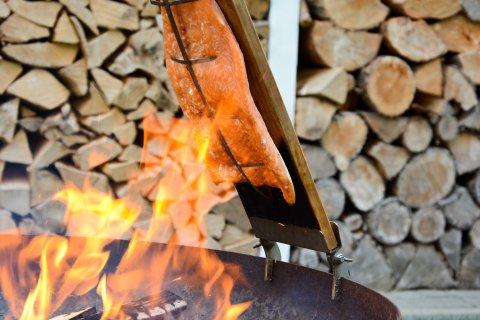 Ein großes Stück Lachs hängt an einer Holzplatte über einem offenen Feuer. Im Hintergrund sind Holzscheite aufgestapelt.