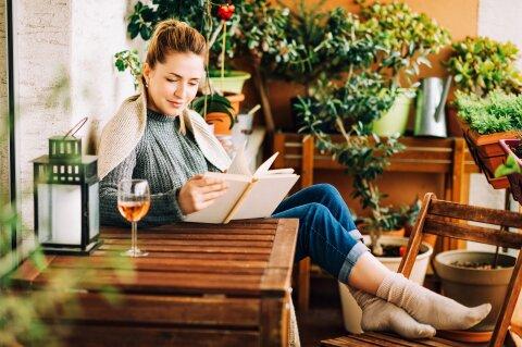 Eine Frau sitzt mit einem Buch und einem Glas Wein auf Holzmöbeln. Um sie herum stehen Pflanzen.