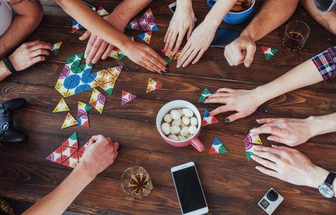 Das Foto zeigt die Hände von verschiedenen Menschen, die an einem Tisch ein Gesellschaftsspiel spielen. Die Aufnahme wurde von oben gemacht.