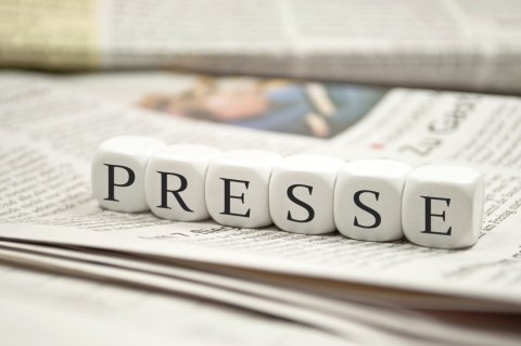 """Auf einer Zeitung liegen Buchstaben-Würfel die das Wort """"Presse"""" bilden."""