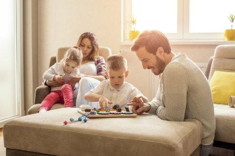 Junge Familie sitzt auf dem Sofa und spielt gemeinsam ein Brettspiel im sonnendurchfluteten Wohnzimmer.