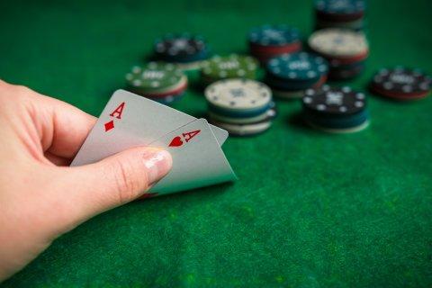 Eine Hand deckt zwei Spielkarten auf. Im Hintergrund Pokerchips.