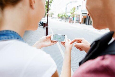Über die Schulter von zwei Personen wird auf ein Smartphone fotografiert.