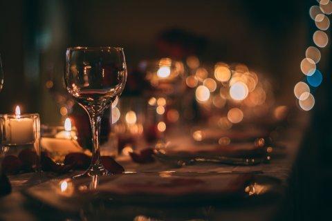 Ein romantisch eingedeckter Tisch mit polierten Gläsern, Kerzenschein und Rosenblättern