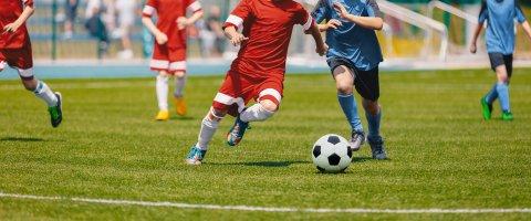 Personen in roten und blauen Trikots spielen Fußball. Ihre Köpfe sind nicht auf dem Bild zu sehen.