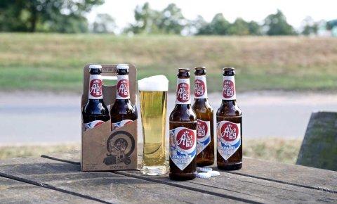 Mehrere Flaschen Ahoi 69 und ein gefülltes Bierglas auf einem Holztisch.