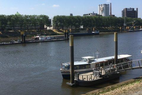 Ein Schiff liegt auf der Weser an einem Anleger