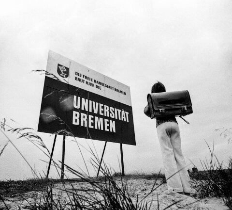 """Schwarz-Weiß Foto von einem Bauschild der Universität Bremen. Darauf stehet: """"Die freie Hansestadt Bremen baut hier die Universität Bremen"""". Davor steht ein Student mit einem Rucksack auf dem Rücken."""