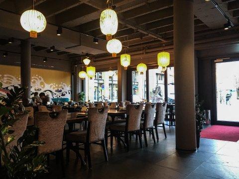 Das Restaurant Yakumi von innen. Man sieht mehrere Tische und asiatische Lampen.