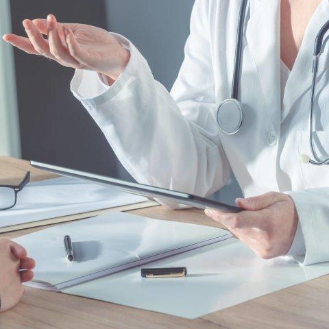 Eine Ärztin erklärt einem Patienten eine Behandlung