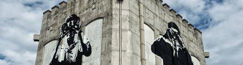 Streetart auf einem Bunker zeigt zwei menschliche Figuren mit Fernglas
