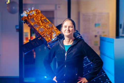 Eine Frau steht vor einem Satelliten.