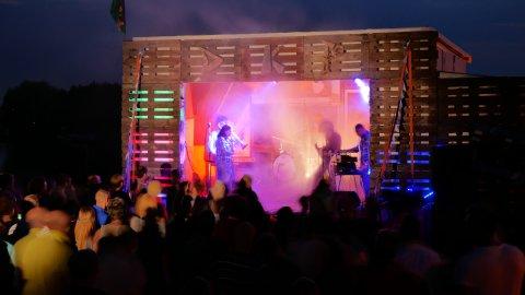 Auf der Bühne der Kompletten Palette steht eine Band und macht Musik.