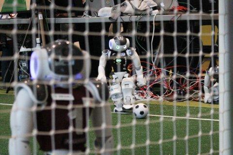 Zwei Roboter mit Fußball vor einem Tor