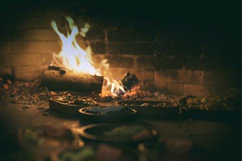 Schälchen mit anatolischen Spezialitäten im Lehmofen, im Hintergrund Feuer.