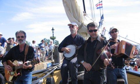 Ein Gruppe Musike vor einem Segelbot