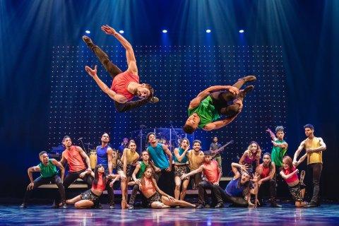 Tänzerinnen und Tänzer posen in bunter Kleidung auf einer Bühne. Im Vordergrund machen zwei Männer einen Salto.